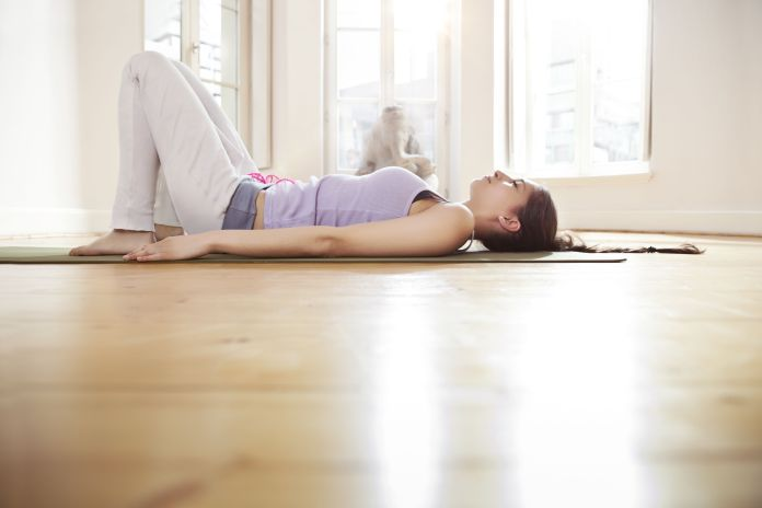 Woman in sunny yoga studio relaxing on her mat