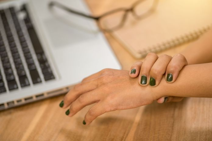 woman painful finger due to prolonged use of keyboard and mouse.