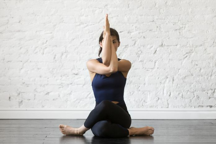 Young attractive woman in Gomukasana pose, studio background