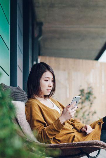 Young beautiful woman using smartphone in balcony