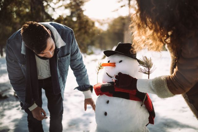 Young friends making snowman in the snow in winter