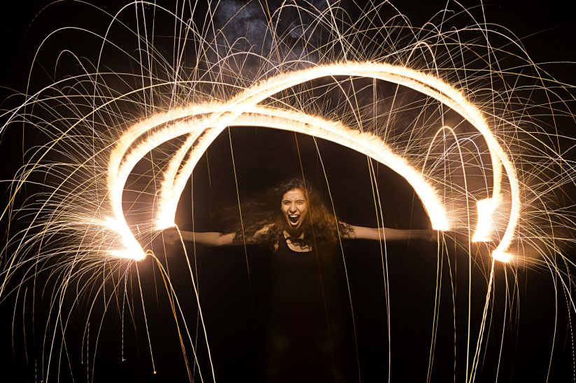 Young woman burning firecrackers during diwali festival