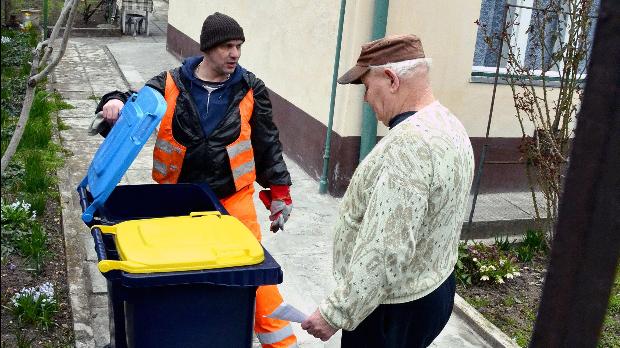 Szücs Zoltán, a Fővárosi Közterület-fenntartó (FKF) Zrt. dolgozója szelektív hulladékgyűjtéshez alkalmas kukákat ad át Budapest X. kerületében, a Bodza utcában 2013. március 25-én. Az FKF munkatársai a fővárosban megkezdték a sárga és kék fedelű, 120 és 240 literes gyűjtőtartályok kiszállítását a házakhoz, amivel a szelektív hulladékgyűjtést oldják meg. MTI Fotó: Balaton József