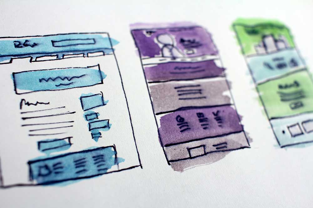 Three wireframes for website layouts done in watercolor on a sketchbook page to show landing pages for self-publishing ebooks