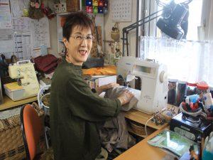 店内のミシンで縫物をする坂口さん