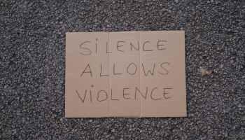 slogan silence allows violence on asphalt road