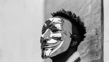 black activist wearing anonymous mask as sign of protest
