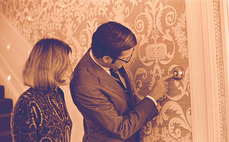 Vintage image showing man and woman inspecting a room thermostat