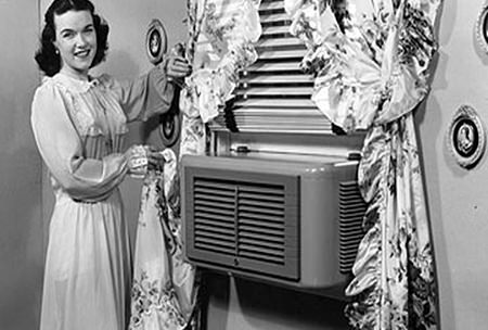 Black and white photo of a woman and an early air conditioning unit