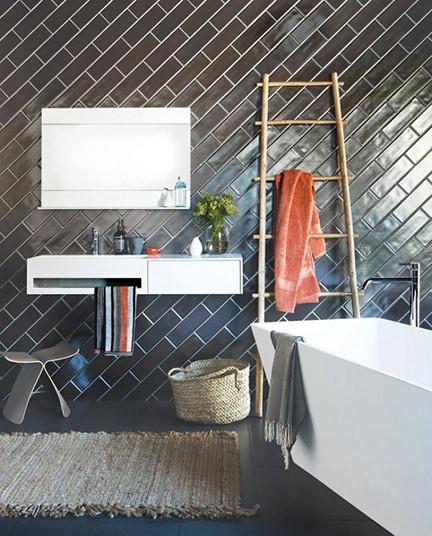 dark tiles on a bathroom wall laid on the diagonal
