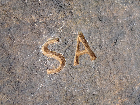Simon Armitage's initials from his 'Rain' poem carved into rock at Cow's Mouth Quarry, near Blackstone Edge on the West Yorkshire/Greater Manchester border