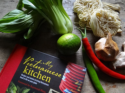 """cover of """"My Vietnamese Kitchen"""" cookery book with dried noodles, pak choi, lime, chilli, ginger and garlic"""