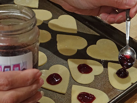 spooning jam on to heart shaped biscuit pastry for jammie dodger hearts