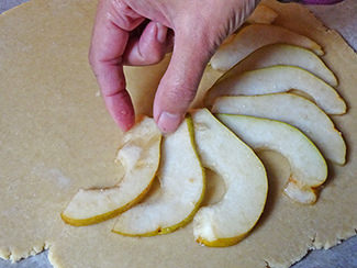 Laying sliced pears on pastry round | H is for Home