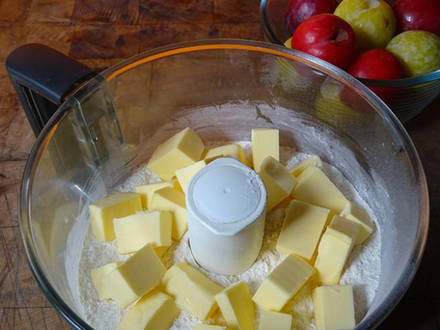 Cubed butter, and flour in a food processor next to a bowl of plums   H is for Home
