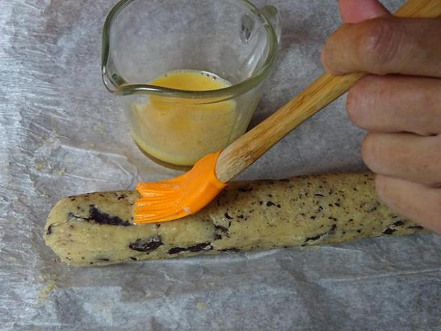 Egg washing log of salted butter chocolate chunk shortbread dough