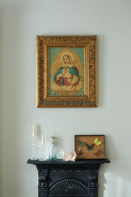 Framed Madonna painting aboove a bedroom fireplace
