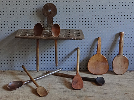 Collection of wooden spoons on an antique wooden spoon rack