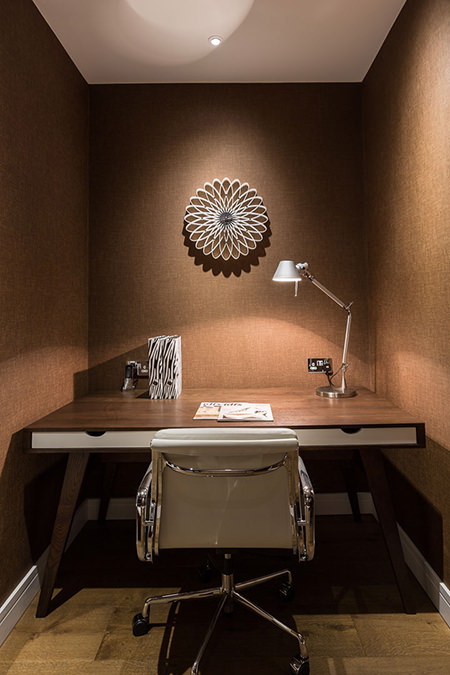 Small home office area with black coffee wallpapered walls