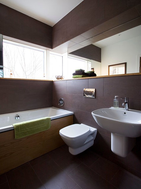Bathroom clad in black coffee stained wood panelling