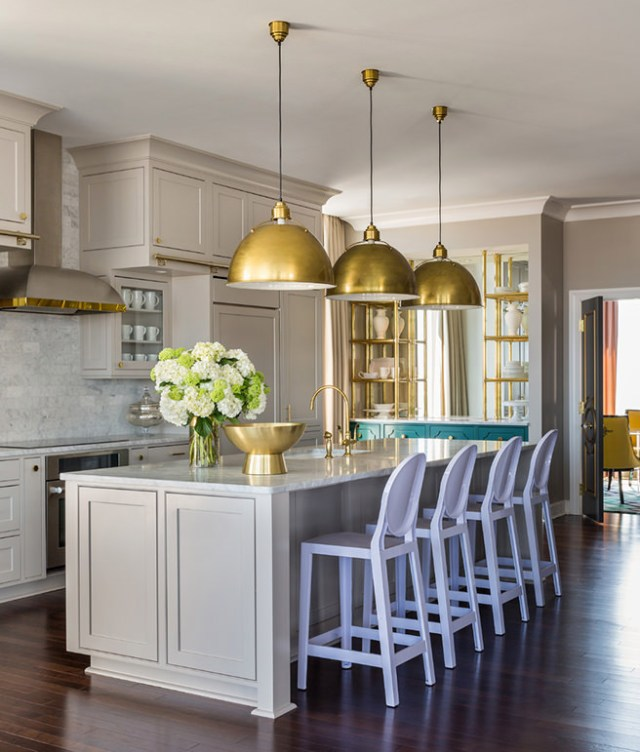 Kitchen with 3 hanging brass lampshades and other brass accessories