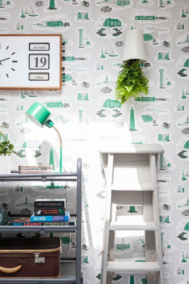 Corner of Mini Moderns' home with white & emerald patterned wallpaper and emerald desk lamp