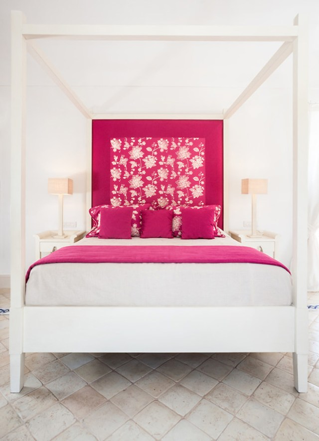 White painted four poster bed with hibiscus pink headboard, cushions and blanket