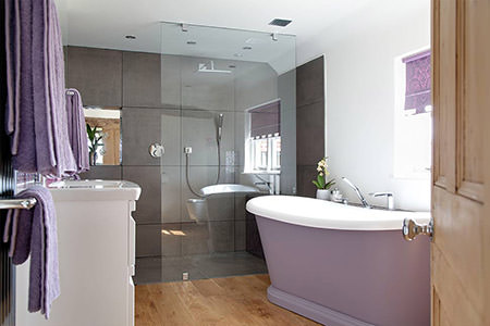 Mauve roll top bath with marching towels and window blind
