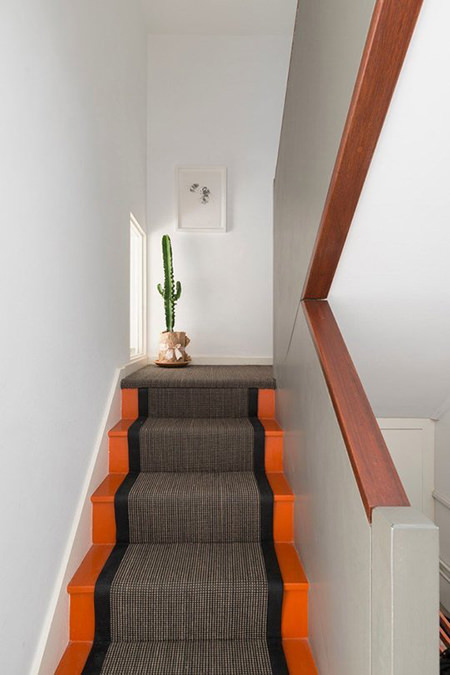 orange painted stairs with grey textile runner