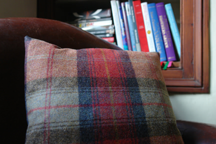detail of a Lois scatter cushion in orange plaid from made.com on a vintage leather club chair
