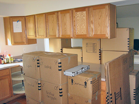 cardboard moving boxes piled up in a kitchen