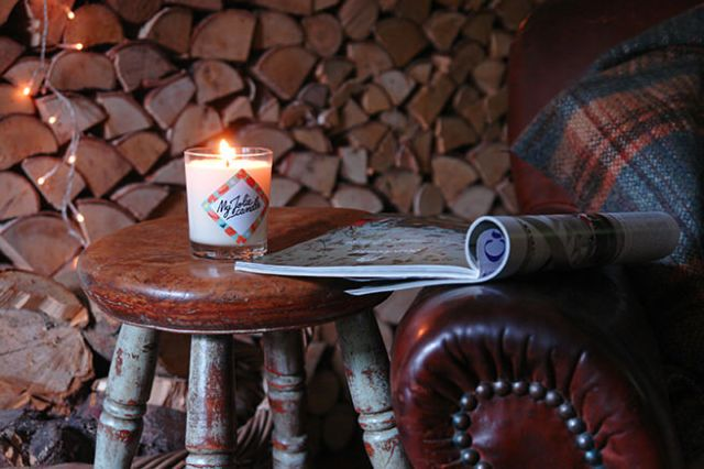 My Jolie Candle lit on a stool next to a leather armchair | H is for Home