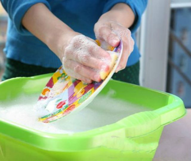 Doing washing up in bright green plastic bowl