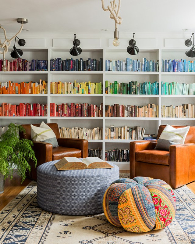 Sitting room with floor to ceiling bookshelves with colour coded books