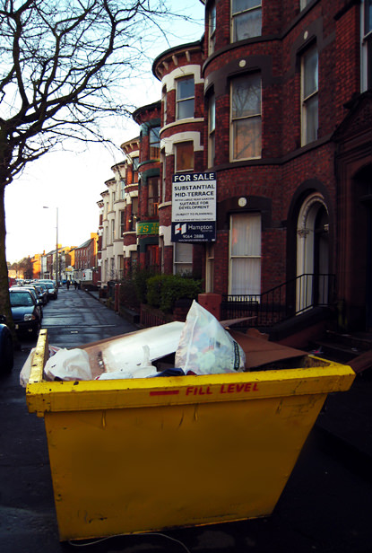 Skip in front of a row of terraced houses