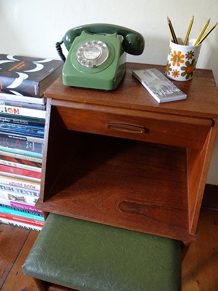 vintage teak telephone table with seat pulled out and green GPO telephone and stack of books