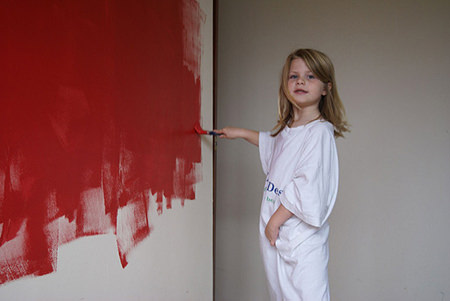 Little girl painting a wall red