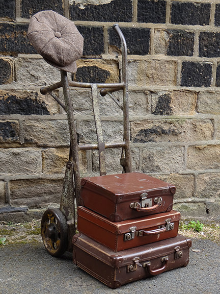 vintage industrial trolley with 3 brown vintage suitcases