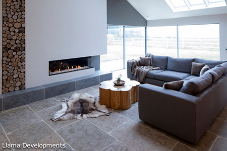 L-shaped sofa in front of a fire with Indian stone tiles with underfloor heating