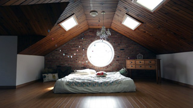 Attic bedroom with circular window and skylights
