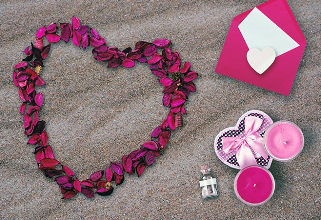 Valentine's Day rose petal heart, card and candles