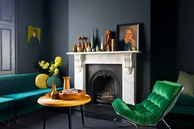Dark-painted living room with emerald velvet upholstered easy chair