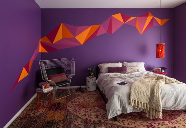 Dramatic bedroom with deep purple painted walls with orange & purple geometric painted feature