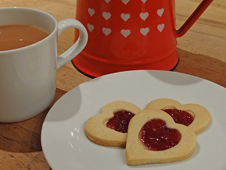 Plate of jammie dodger hearts and mug of tea