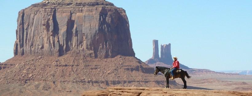 photo d'un cowboy sur son cheval devant un paysage du Grand Ouest des Etats-Unis