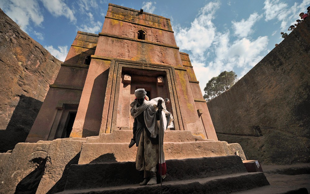 An Ethiopian Orthodox Christian pilgrim leaves the rock-hewn church Bete Giyorgis after attending a mass before the annual festival of Timkat in Lalibela, Ethiopia which celebrates the Baptism of Jesus in the Jordan River, on January 19, 2012. During Timkat, the Tabot, a model of the Ark of the Covenant is taken out of every Ethiopian church for 24 hours and paraded during a procession in towns across the country. Over 80 % of Ethiopians are estimated to be Orthodox Christians. Ethiopian Orthodox Christians believe the real Ark of the Covenant ( a vessel containing the Ten Commandments)  is held in Aksum. It is guarded by a select group of monks, whose sole commitment is to protect the sacred vessel. AFP PHOTO/CARL DE SOUZA