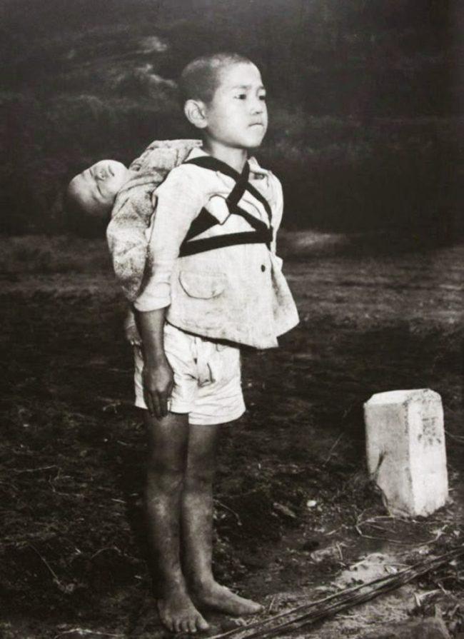 Huérfano con su hermano a la espalda