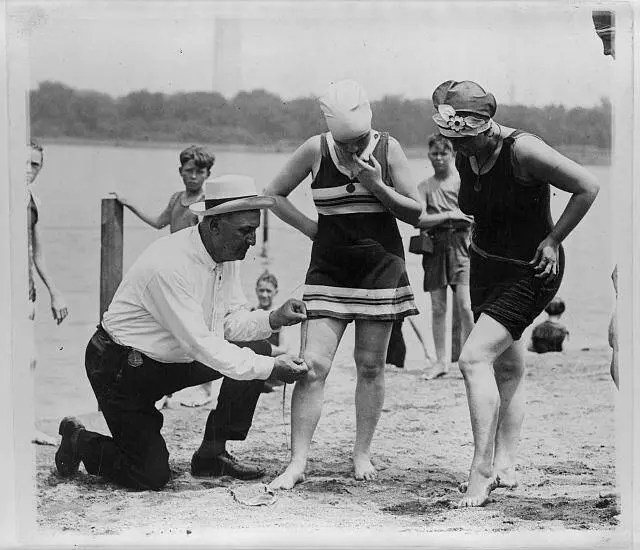 A policeman measures the distance between a woman's knee and the bottom of her bathing suit, 1922.