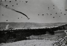 More German paratroops landing on Crete, dropped from Junkers 52 transports, 20 May 1941. Taken by a British combat photographer, the photo was edited for propaganda purposes to show a black smoke trail from a damaged Ju 52. Several were indeed lost by anti-aircraft fire during the airdrops but none were hit at the time this picture was taken.