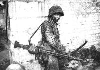 A German SS Landser involved in heavy fighting in and around the French town of Caen during the summer of 1944. He is carrying an MG 42 configured as a light support weapon with a folding bipod and detachable drum belt container.